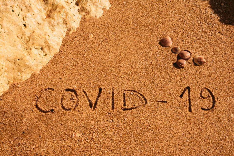 Travel and tourism concept for pandemic alert, flights and trips cancellation. Text written on the sandy...
