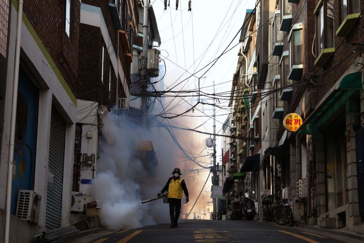 A South Korean man in Seoul disinfects an alley to prevent the spread of coronavirus, March 18, 2020.