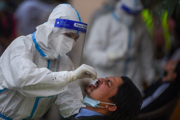 Una sanitaria extrae una muestra a un periodista para hacerle la prueba de PCR en Katmandú
