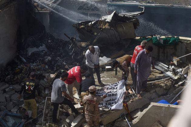 Pessoas resgatam vítima do acidente com voo comercial no centro de