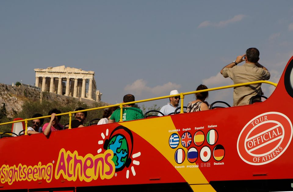 In this photo taken on Wednesday, June 9, 2010 tourists take photos of the ancient Parthenon temple on...