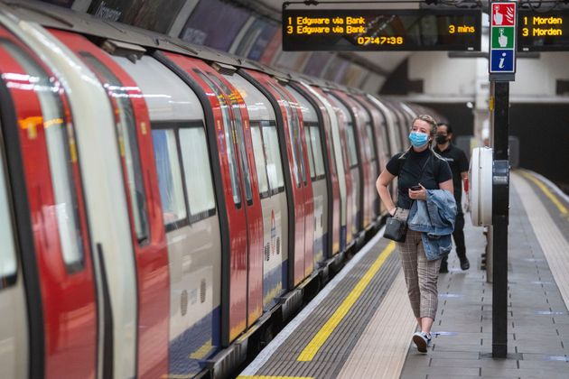 A commuter wearing a protective face mask walks along the platform at Clapham Common underground station,...
