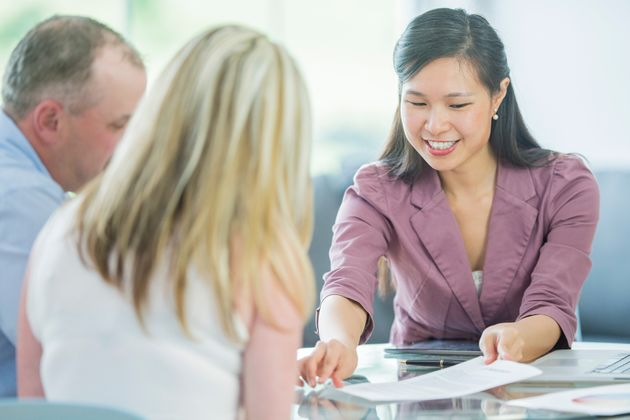 A couple gets from mortgage advice from a financial services representative in this stock image. A...