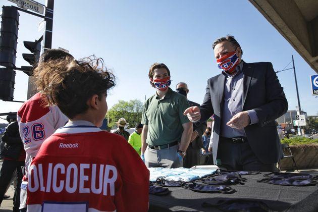 Jonathan Drouin et François Legault distribuant des