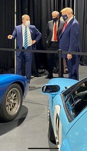 Bill Ford Jr., executive chairman of Ford Motor Co., points to a collection of Ford GT vehicles while talking with President