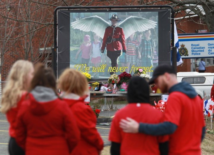 Mourners, asked to wear red, are seen near a mural dedicated to slain RCMP Const. Heidi Stevenson, during a province-wide, two-minutes of silence for the 22 victims of last weekend's shooting rampage, in front of the RCMP detachment in Cole Harbour, N.S. on April 24, 2020.