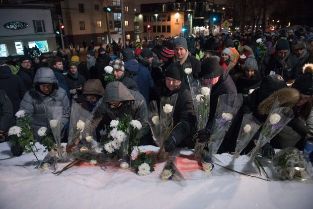 People lay flowers in memory of the victims near the Islamic Cultural Centre in Quebec City on Jan. 29,