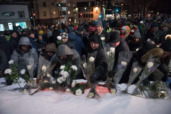 People lay flowers in memory of the victims near the Islamic Cultural Centre in Quebec City on Jan. 29, 2018.