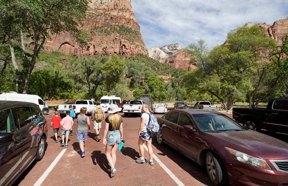 Visitors leave the Zion Lodge parking lot to go on hike in Zion National Park on May 15 in Springdale,...