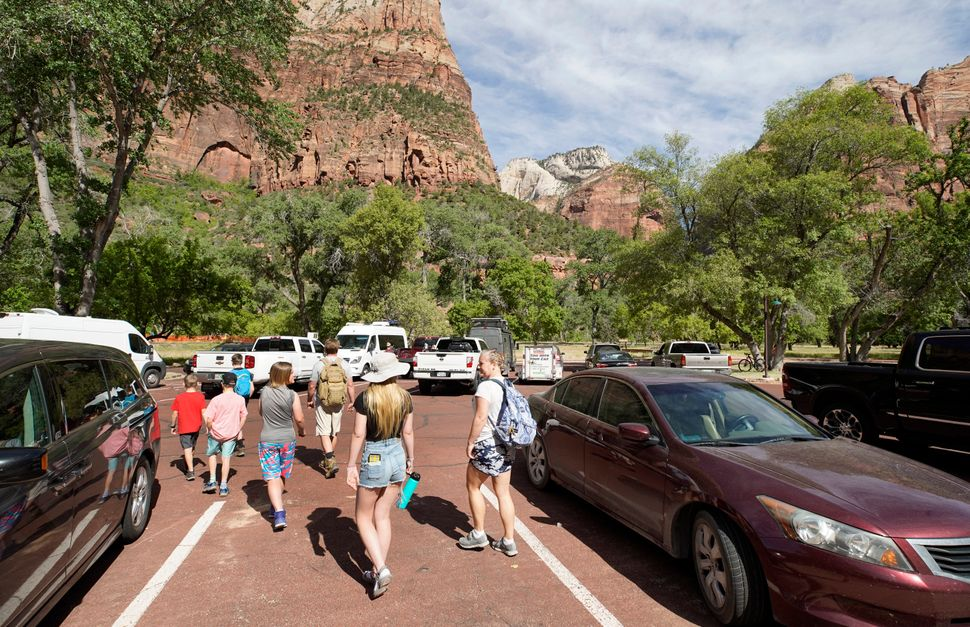 Visitors leave the Zion Lodge parking lot to go on hike in Zion National Park on May 15 in Springdale, Utah. Zion National Pa