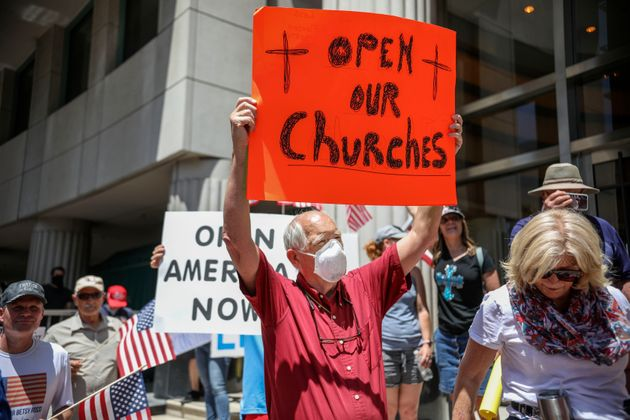 Demonstrators holding signs demanding the reopening of churches during a rally on May 1, 2020, in San