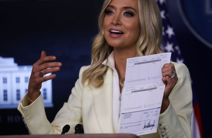 "White House press secretary Kayleigh McEnany holds up a donation check signed by Donald Trump for $100,000 made out to the ""O"