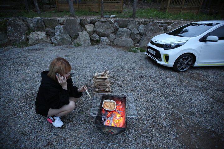 캠핑장 화롯불에 라면을 끓여 먹는 김주현씨.