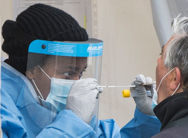 Un travailleur de la santé se prépare à prendre un échantillon sur un homme, dans une clinique de test...