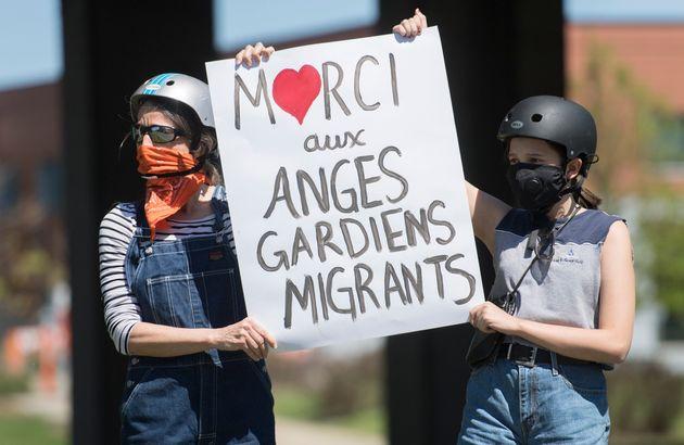 Des gens brandissent une pancarte alors qu'ils assistent à une manifestation devant le bureau de circonscription...