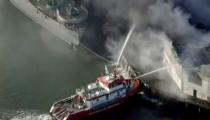 First responders battle a massive fire that erupted at a warehouse early Saturday, May 23, 2020 in San Francisco.
