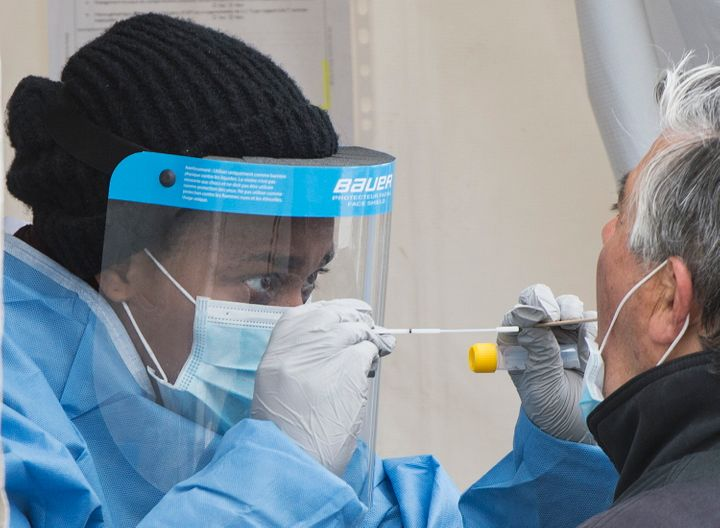 A health-care worker prepares to swab a man at a walk-in COVID-19 test clinic in Montreal on May 10, 2020.