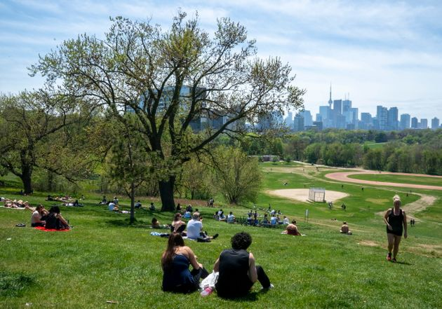 Park visitors soak up the sun in Toronto on May 23, 2020. Warm weather and a reduction in COVID-19 restrictions...