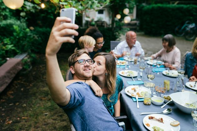 A couple taking a selfie with a smartphone during a barbecue with the