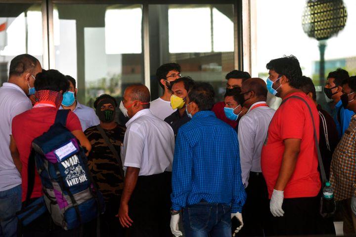 Passengers gather around an Air India official as their flight was cancelled at Chhatrapati Shivaji Maharaj International Air