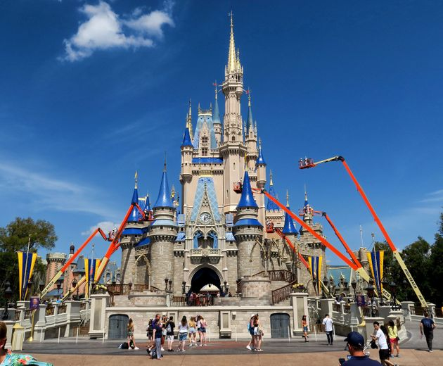 Workers at Walt Disney World paint Cinderella Castle in the Magic Kingdom, in Lake Buena Vista, Fla.,...