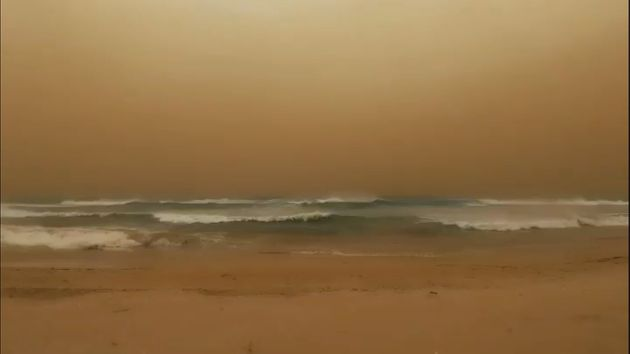 Waves crash to shore as a dust storm blows towards the sea in Geraldton, Western Australia, in this still...