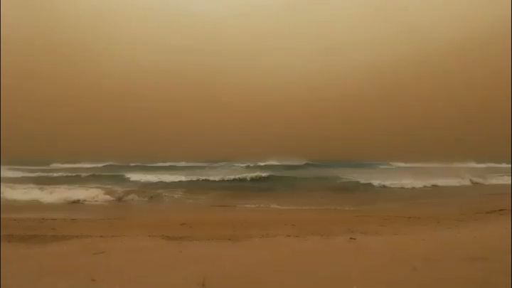 Waves crash to shore as a dust storm blows towards the sea in Geraldton, Western Australia, in this still image taken from a May 24, 2020 video obtained from social media. Chris Lewis/via REUTERS