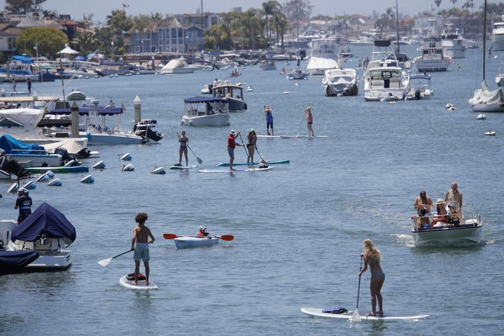 Boaters and paddle boarders use a harbor Sunday, May 24, 2020, in Newport Beach, Calif. (AP Photo/Marcio Jose Sanchez)