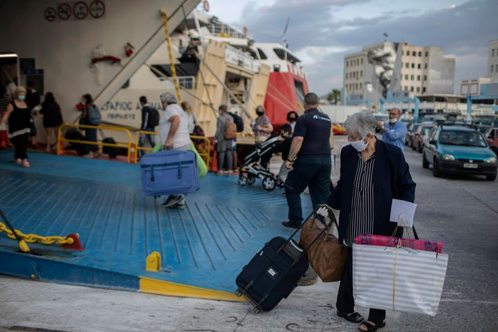 Passengers wearing mask to reduce the spread of the coronavirus board a ferry at the Piraeus port near Athens on Monday, May
