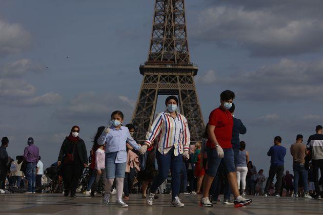 Un grupo de turistas frente a la torre Eiffel, en