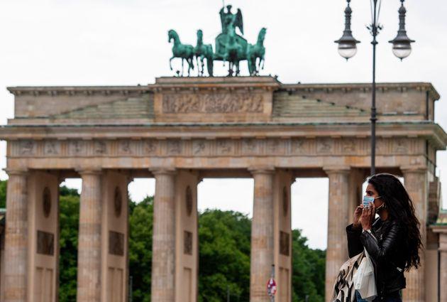 Una mujer pasea por delante de la Puerta de Brandenburgo, en