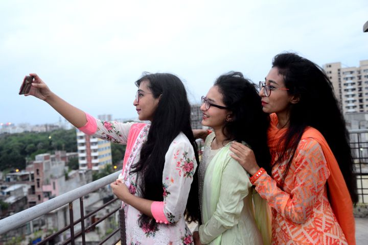 Muslims girls wearing new dresses take a selfie to celebrate in Dhaka, Bangladesh, on Monday.