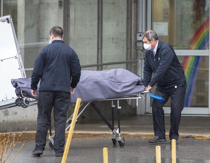 Funeral home workers remove a body from the Centre d'hebergement Ste-Dorothee on April 13, 2020 in Laval, Que.