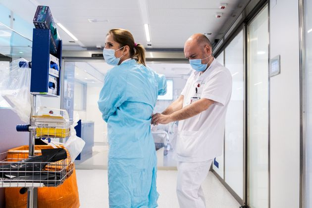 Un enfermero ayuda a su compañera a quitarse el EPI en un hospital de