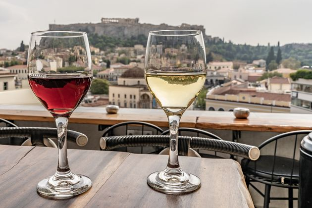 Glasses of wine with a view of the Acropolis in Athens, Greece. Red and white wine. Wide angle close