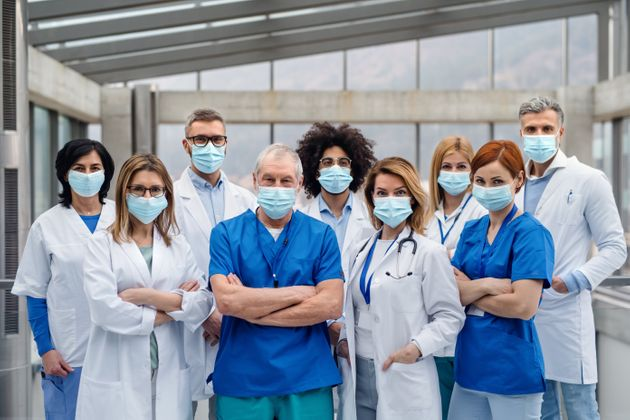 A group of doctors with face masks looking at camera, corona virus
