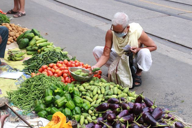 People buy vegetables from a market in Kolkata after the government eased lockdown on May 25,