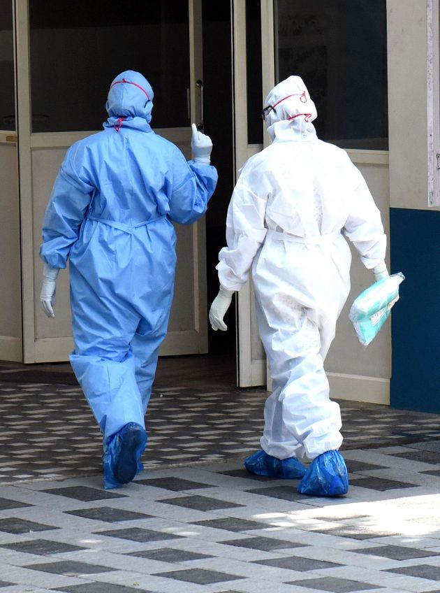 Medical workers wearing protective suits seen outside a special isolation ward of a Hospital in...