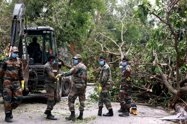 Army Jawans work to clear trees uprooted by cyclone Amphan from a road in Kolkata after cyclone Amphan...