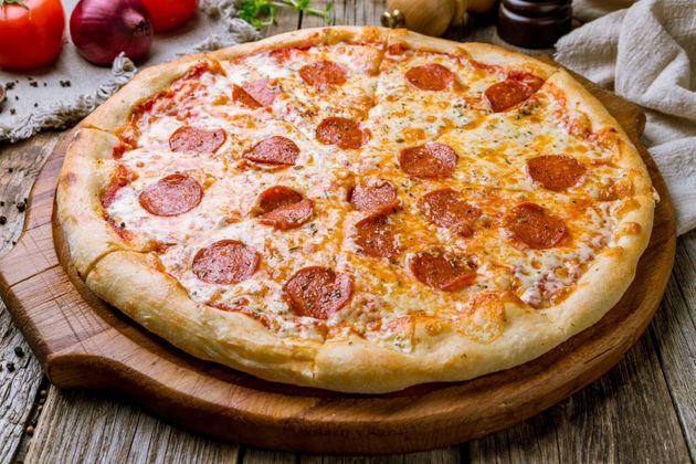 Pepperoni pizza on board on wooden
