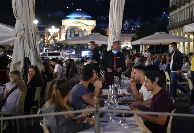 Persone nei dehor dei locali della movida in piazza Vittorio nel primo giorno di riapertura, Torino,...