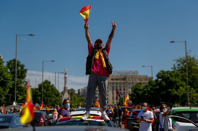 Un hombre alza los brazos en señal de protesta en la caravana #GobiernoDimision de