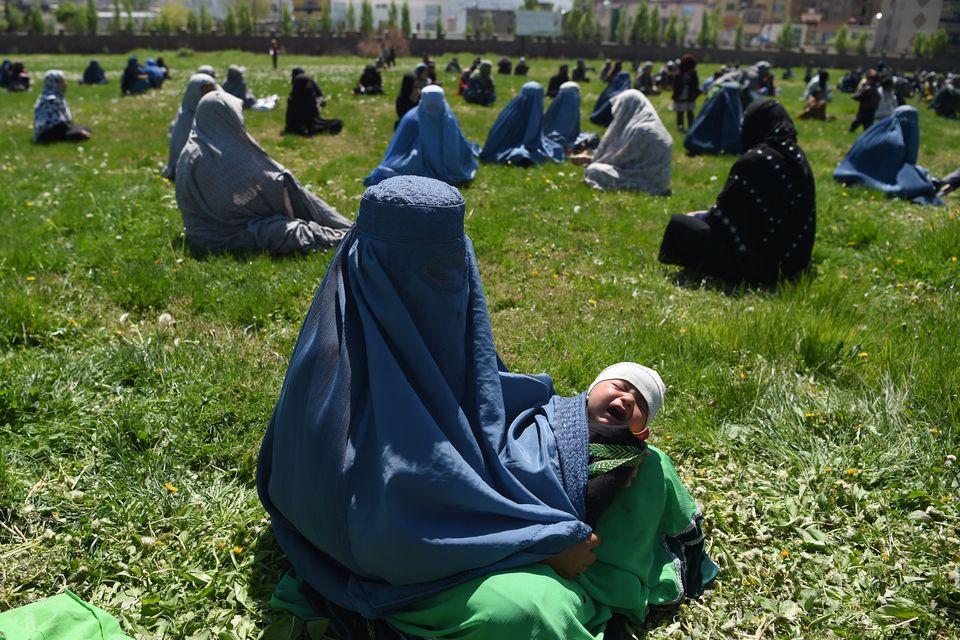 Γυναίκα με μπούργκα κρατά στην αγκαλιά ένα μωρό καθώς περιμένει να λάβει δωρεάν δημητριακά από κρατικές υπηρεσίες του Αφγανιστάν, εν μέσω πανδημίας