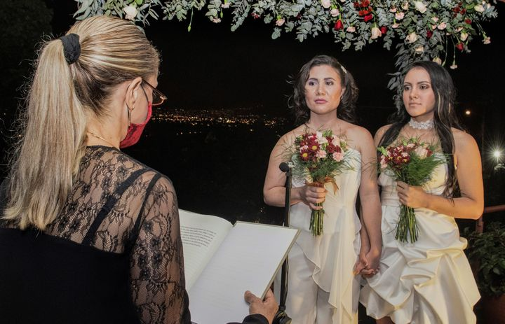 Alexandra Quiros (C) and Dunia Araya (R) stand before a lawyer during their wedding in Heredia, Costa Rica, Tuesday.