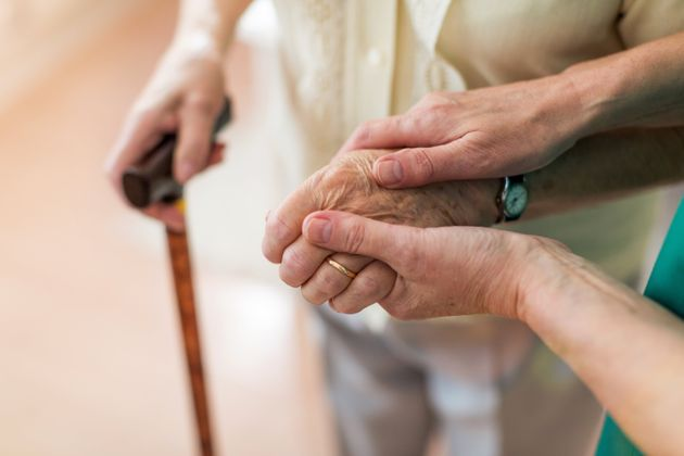 Nurse consoling her elderly patient by holding her