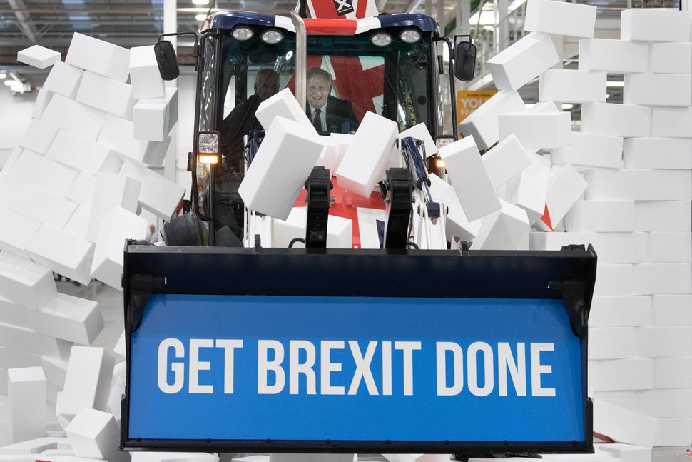 """Johnson driving a Union flag-themed JCB, with the words """"Get Brexit Done"""" inside the digger bucket, through a fake wall embla"""
