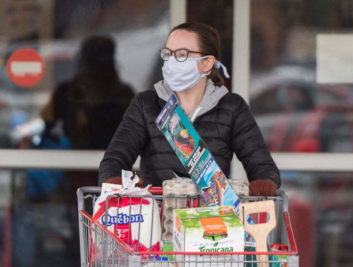 A woman wears a mask as she leaves a grocery store in Montreal on April 10.