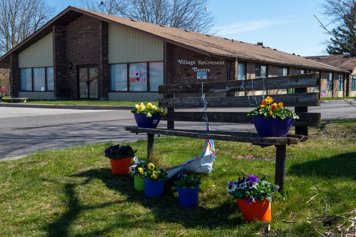 Flowers sit on a bench in front of Orchard Villa care home in Pickering, Ont., on April 27, 2020. This facility is one of five mentioned in a new report on long-term care homes in Ontario.