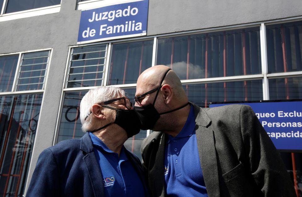 Marcos Castillo (à esq.) e seu marido Rodrigo Campos (à dir.) se beijam com máscaras...