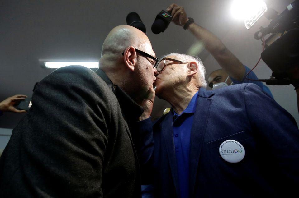 Marcos Castillo (à esq.) e seu marido Rodrigo Campos (à dir.) se beijam, agora, sem máscaras...